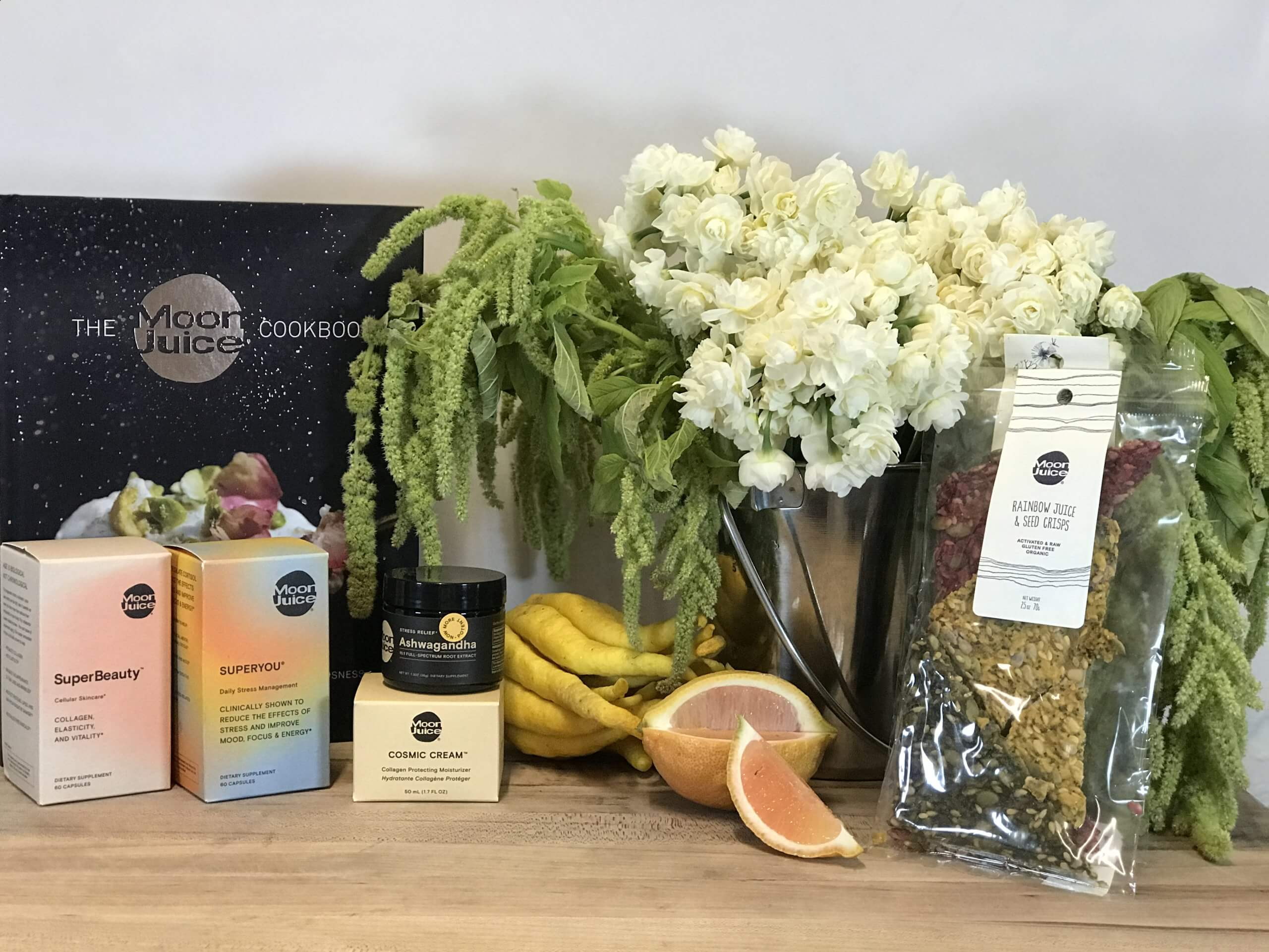 Moon Juice cookbook and other natural products with vase of flowers