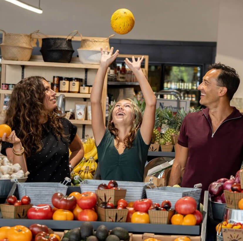 woman, child and man in store with produce