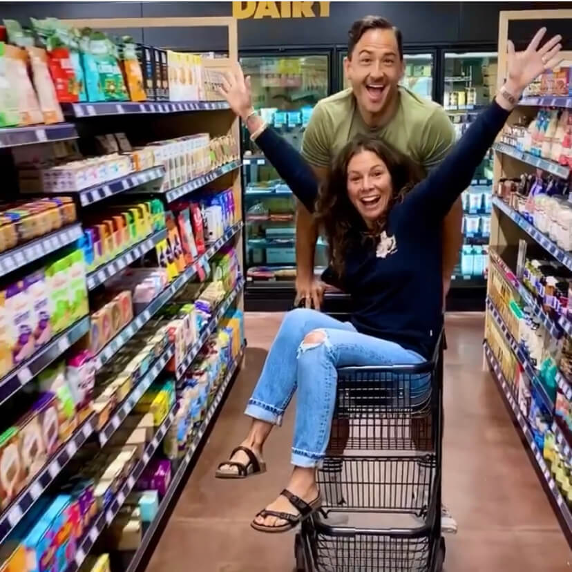 Woman in grocery cart with arms raised